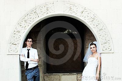 Bride and groom standing under white arch