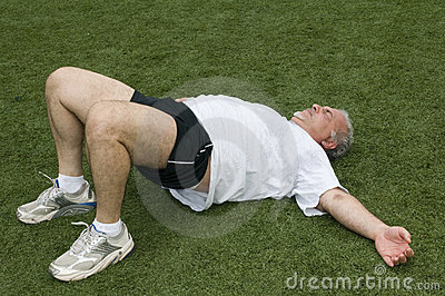 Middle age man stretching   sports field