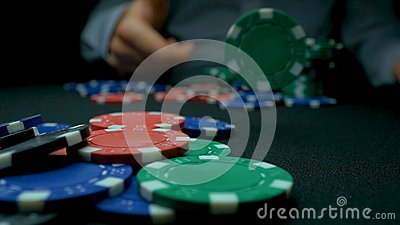 Throw the blue chips in poker. Blue and Red Playing Poker Chips in Reflective black Background. Closeup of poker chips