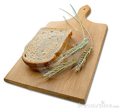 Rye ears (spikes) and loafs of bread on wooden board