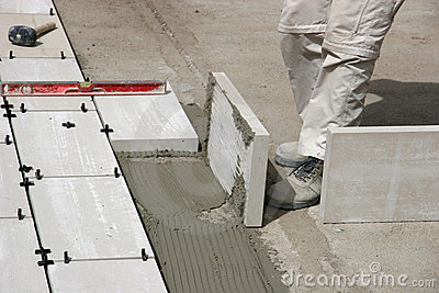 Legs of worker laying tiles