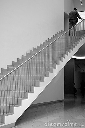 Men climbing up stairs in library (b/w)