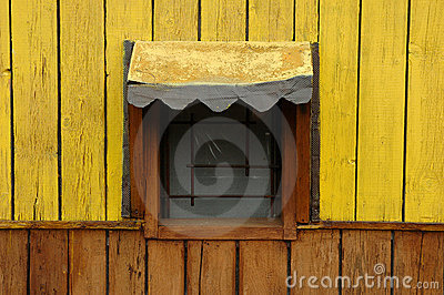 Yellow window of a wooden cottage