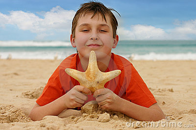 Boy on beach holding a sea star
