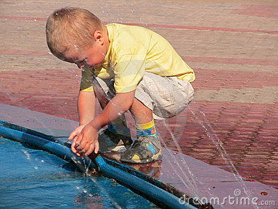 Boy playing with fountain