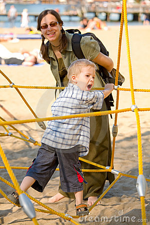 Boy on yellow ropes with mom