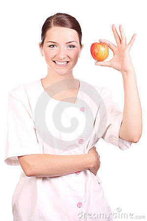 Nurse smiling and holding up an apple