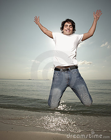 Young man jumping by the sea shore