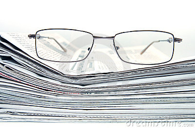 Pile of newspaper with eyeglasses