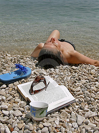 Woman with book on beach