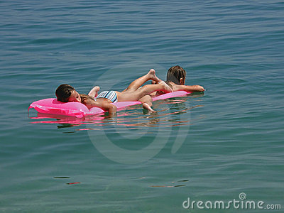 Twins with pink matrass on sea