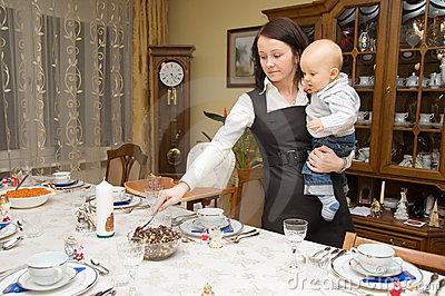 Woman setting table with her child