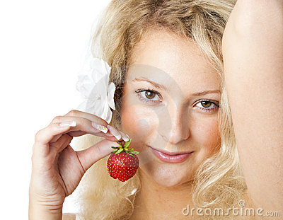 Young woman in white dress eating strawberries