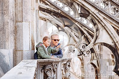 Father with son tourists are on the roof of Milan Cathedral