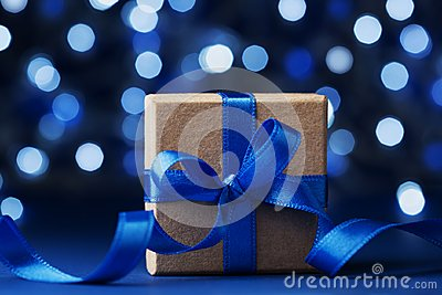 Christmas gift box or present with bow ribbon against blue bokeh background. Magic holiday greeting card.