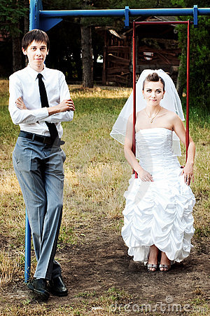 Bride and groom leaning on swings