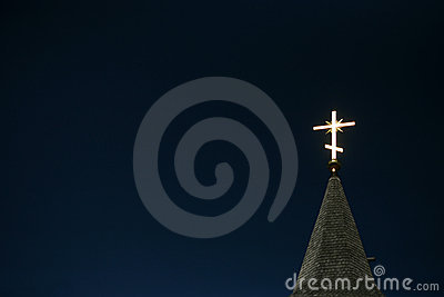 Lighting orthodox cross on a blue sky