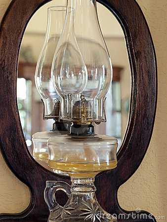 Old glass hurricane lamp reflected in mirror