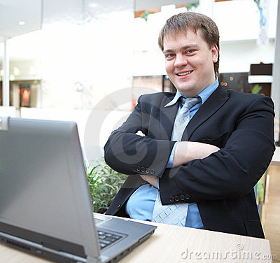Happy young businessman with laptop
