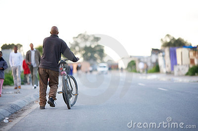 Black man with a bicycle.