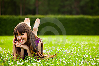 Pretty smiling girl is laying on green grass
