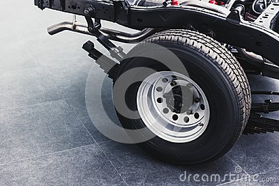 Close up pickup truck rear tire with car chassis underbody