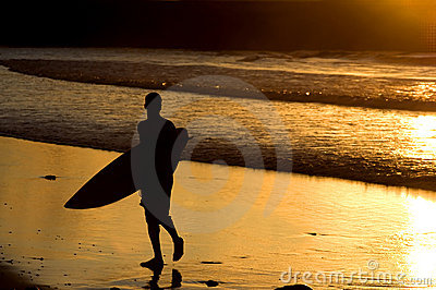 Silhouette of surfer at a yellow sunset