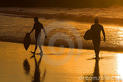 Silhouette of two surfer at yellow sunset