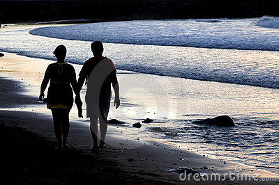 Couple silhouette walking at the seaside at sunset
