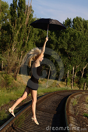 Woman in black dress flying on an umbrella