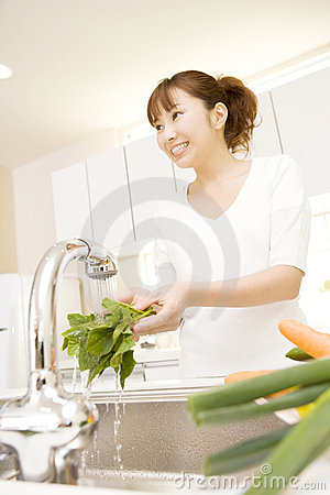 Japanese woman washing a vegetable