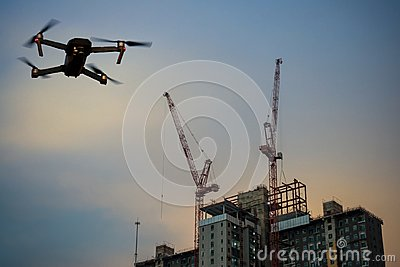 Construction site building with crane and drone