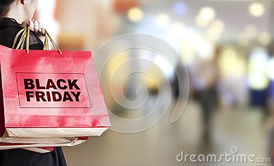 Young woman holding black friday shopping bag