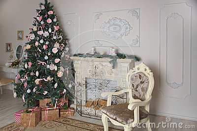 Interior of the living room with a fireplace, decorated for the New Year with a big Christmas tree and lots of presents