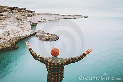 Man enjoying cold sea view alone raised hands