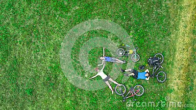 Family cycling on bikes outdoors aerial view from above, happy active parents with child have fun and relax on grass