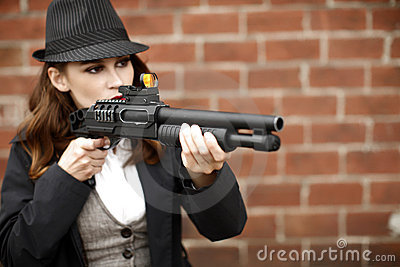 Stylish woman pointing shotgun