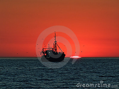 Boat in front of a sunset at the horizon