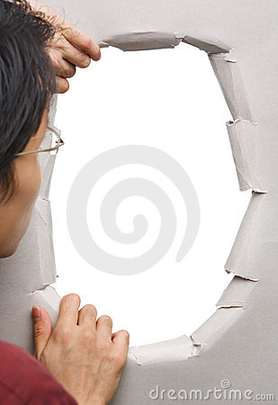 Man peeking through hole in wall
