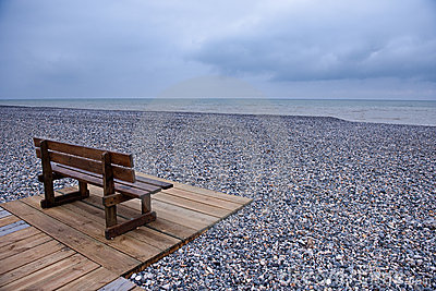 Wooden bench at a pebbles beach