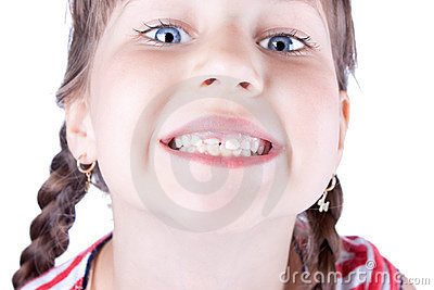 Closeup of a cute small girl showing her new tooth