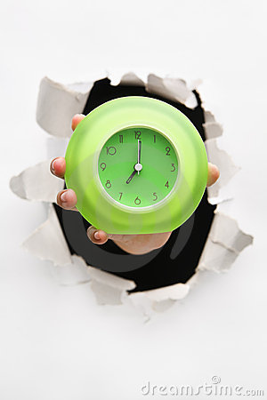 Hand breakthrough wall holding green clock