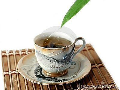 A cup of tea and drops isolated on white