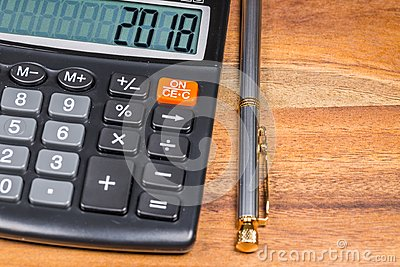 Calculator with 2018 number And Ballpoint Pen Branch On Wooden Table. Close Up