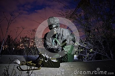 Man in protective chemical clothing and isolated gas mask with chemical detection device in zone of chemical contamination