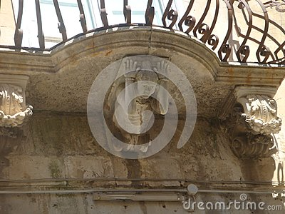 Characteristic balcony of Ragusa Ibla with under a statue that seems to hold up it. Sicily. Italy.