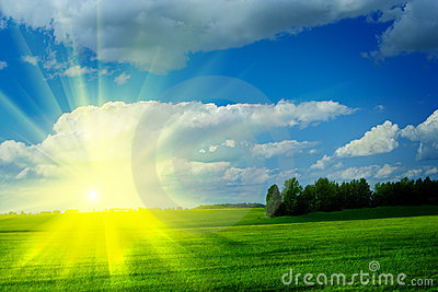 Sunrise on a meadow with beautiful cloudy blue sky