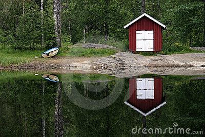 Boat house reflecting on lake