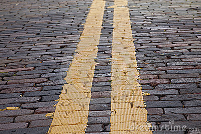Yellow stripe on brick street