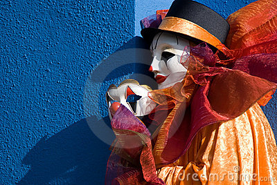 Clown holding mask in front of blue wall